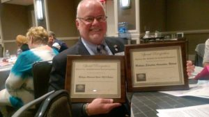 Secretary Treasurer Dan Rudd Holding the awards for the MEA - Retired website and newsletter
